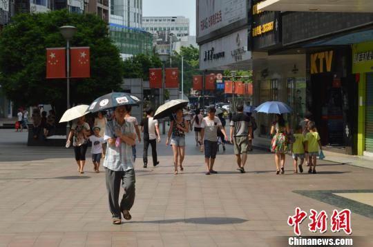 图为市民带遮阳伞出行。韦东明摄