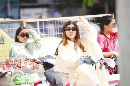 """7月23日南宁酷热难耐,民主路上两位骑着电动车的女士虽""""全副武装"""",仍忍不住用手遮阳。记者 邹财麟 摄"""