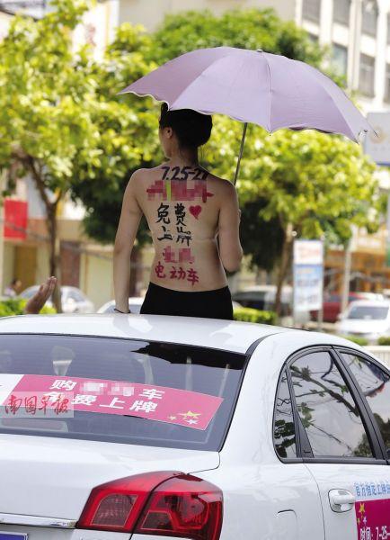 """""""彩绘女""""背部满是广告语。 记者 苏华 摄"""