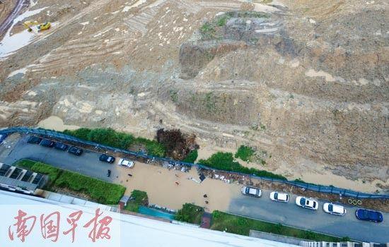 """小区临时搭建的围栏边靠近高高的""""泥山""""。图片来源:南国早报"""