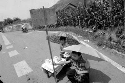 两个孩子在骄阳下打着伞摆茶摊。京华时报记者陶冉摄