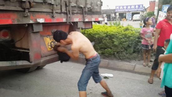 司机张某用衣服擦掉机油。覃成朝 摄