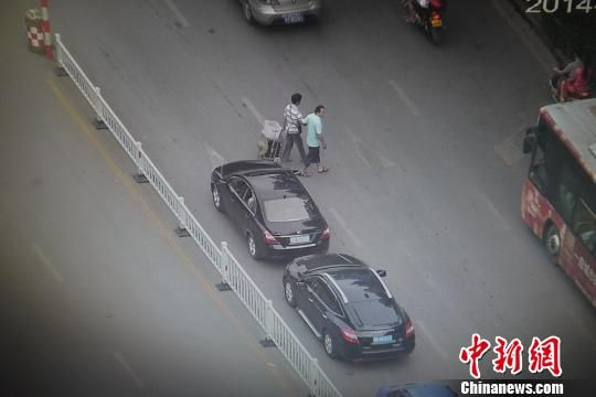 8月7日早上,广西柳州市屏山大道上,市交通监控中心高空摄像头拍摄到一名私家车主停车搀扶一位盲人过马路的场景。 韦东明 摄