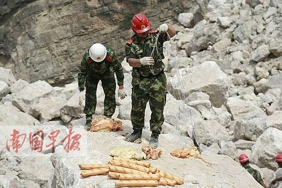 官兵整理炸药,准备爆破巨石。李斌 摄