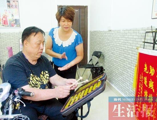 卢莎在教残疾学生学小钟琴。图片来源:当代生活报