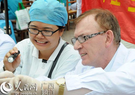 广西医科大学口腔医学院学生协助来自澳大利亚的世界卫生组织特聘口腔专家詹姆斯・罗伯逊,为靖西群众检查口腔。