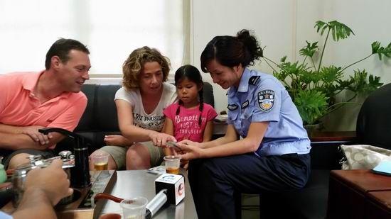 李莎玲一家和民警屈玉华在交谈。黄荣平 摄