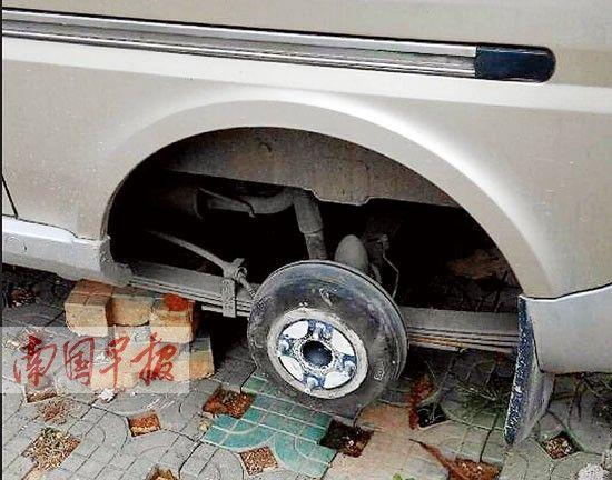 小车后轮被盗,车身被人用砖头顶了起来。 记者 魏碧锋 摄