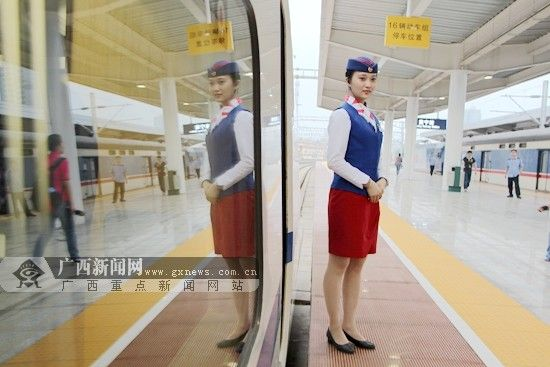 """""""坐动车""""将成为广西民众中秋期间出行首选。图为""""动姐""""在高铁动车旁等待旅客上车。广西新闻网 资料图"""