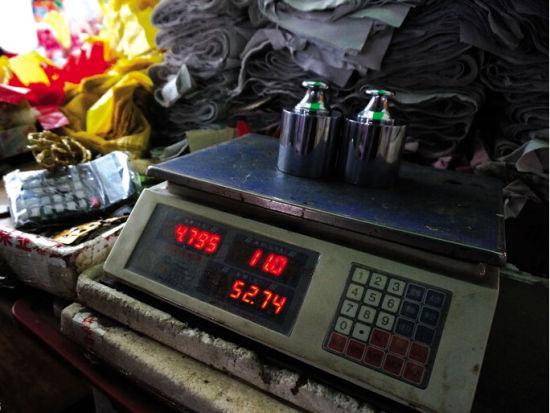"""4公斤的计量砝码,该""""黑心秤""""显示约4.8公斤 南国早报记者 雷倩倩摄"""