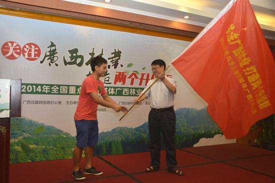 自治区互联网信息办公室主任金化伦向媒体记者代表授旗