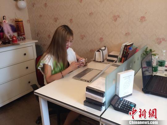 曾雪正在自己的工作室用手机与客户谈生意 殷樱 摄