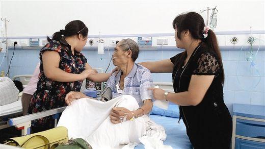 家人正在护理病床上的蒙桂军。图片来源:南国早报