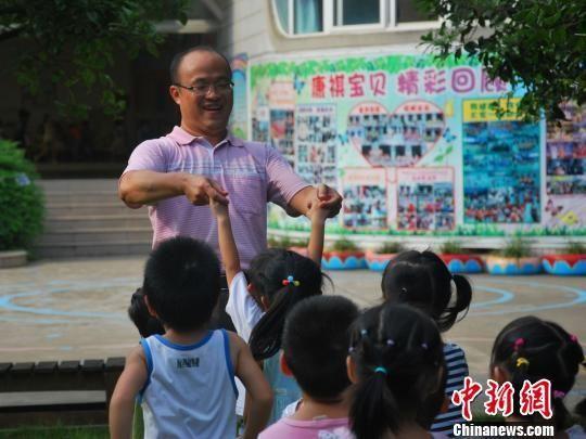 9月4日,广西柳州一家幼儿园唯一一名男幼师傅祥慧正在与孩子参加课外活动。 朱柳融 摄2