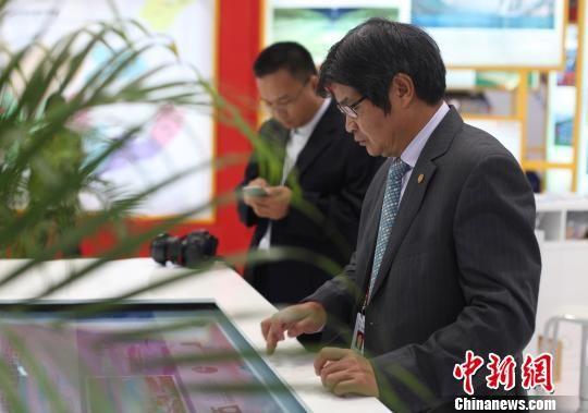 图为泰国嘉宾在中广核集团展厅点击触摸屏了解该集团项目布局、在建及在运机组的情况。 黄穗芳 摄