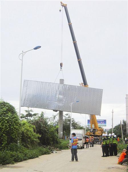 工作人员正在吊拆非法广告牌。 张文卉 摄