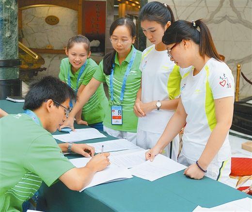 9月24日,在南宁明园新都酒店,两名志愿者(穿白衣服者)正在配合工作人员进行媒体记者接待演练。