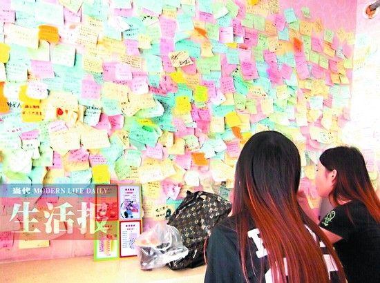 两名年轻女顾客在看墙上留言。图片来源:当代生活报