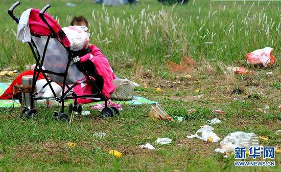 """郑州黄河国家湿地公园内的草地上随处可见游人丢弃的垃圾(10月4日摄)。国庆长假期间,部分游客乐享旅游的同时,在公共场所乱丢垃圾,成为假日里的""""不和谐""""现象。 新华社记者李安摄"""