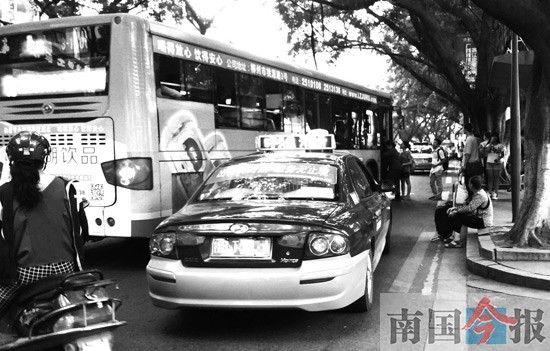 """解放北路,出租车前后""""夹击""""停靠在公交站台旁,影响公交车进出站。记者 卿要林 摄"""