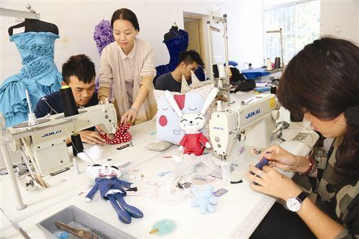 老师在指导学生用旧衣服布料制作手工艺品