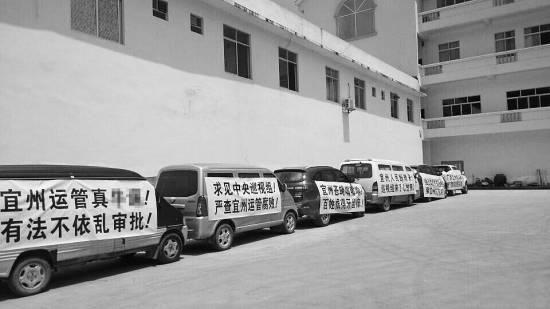 """今年7月,宜州市运管局通过了当地另一家车检企业开展营运车辆综检业务的备案,引发原来""""独家垄断""""河池综检市场的企业的不满,其员工打出各种抗议标语。"""