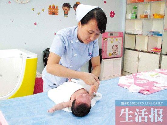 腾蓝兰在给宝宝做抚触。图片来源:当代生活报