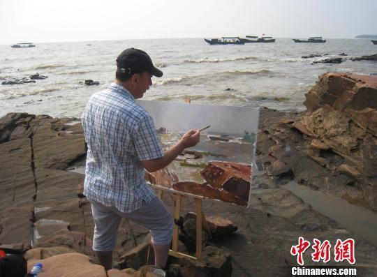图为画家在广西防城港簕山古渔村挥洒笔墨进行创作。李敏军 摄