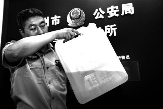 陈某用15公斤容量的塑料壶装满了汽油,并已倒出约三分之二。民警将剩余的汽油带回派出所。张存立 摄
