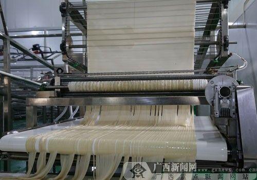 """生产线一端""""吐""""出的米粉被切成""""扁粉""""状。"""