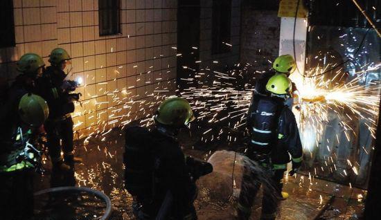 消防官兵赶来用切割机破门救火。
