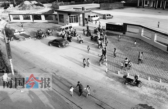 学校门口就建在马路的一个坡顶上。 记者 颜篁 摄