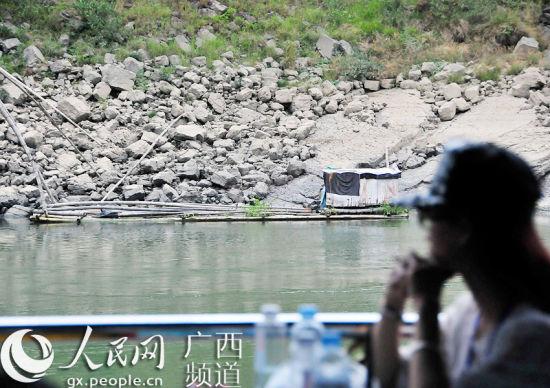 大藤峡游船上的游客正在凝视岸边破旧的竹筏。大藤峡水利枢纽完工后,此地将能航行千吨级以上船舶