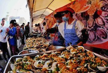 在钦州美食街,厨师在加工大蚝食品。新华社记者 张爱林 摄