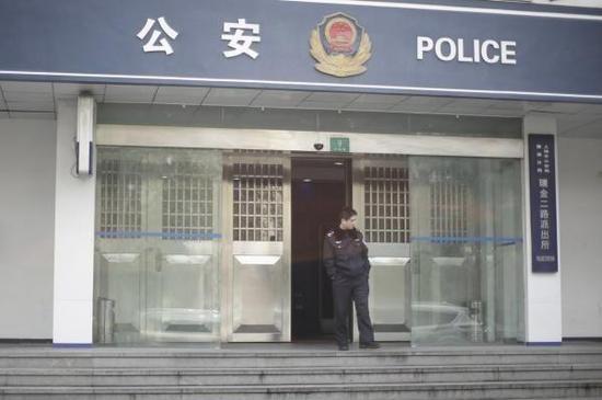 一位民警站在瑞金二路派出所门口,高峰正在派出所内。 澎湃新闻记者 杨一 图